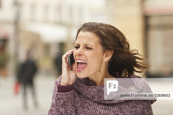 Woman using mobile phone  screaming  close-up