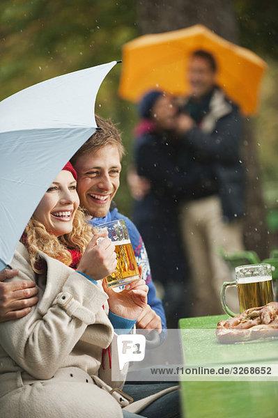 Englischer Garten  Vier Personen im verregneten Biergarten  Frau hält Bierkrug  lächelnd  Porträt Englischer Garten, Vier Personen im verregneten Biergarten, Frau hält Bierkrug, lächelnd, Porträt