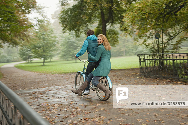 Germany  Bavaria  Munich  English Garden  Couple riding bicycle