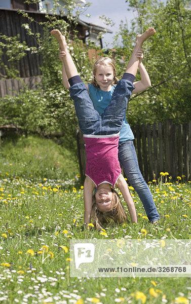 Österreich  Salzkammergut  Zwei Mädchen (10-11) im Garten  Freundin beim Handstand helfen