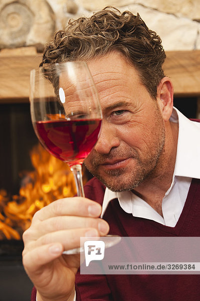 Man holding glass of red wine by fireplace  portrait  close-up