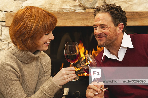 Couple drinking red wine by fireplace
