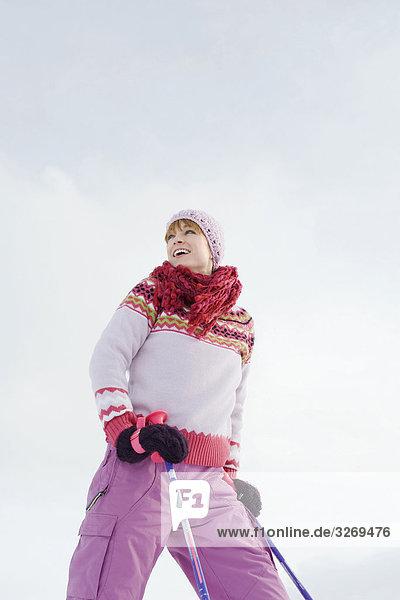 Italy  South Tyrol  Seiseralm  Woman holding ski poles  smiling  portrait