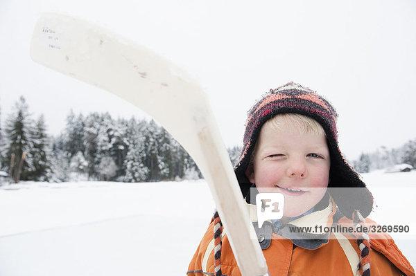 Italy  South Tyrol  Seiseralm  Boy (4-5) holding hockey stick  portrait  close-up