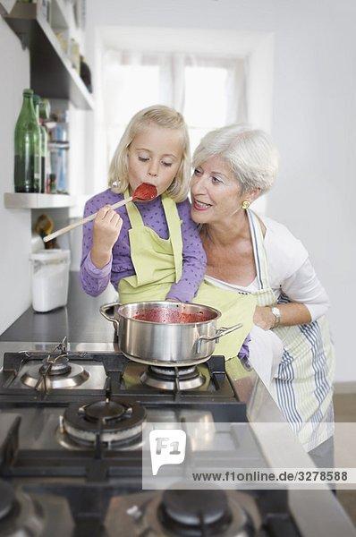 Mädchen mit Großmutter Kochmarmelade Mädchen mit Großmutter Kochmarmelade