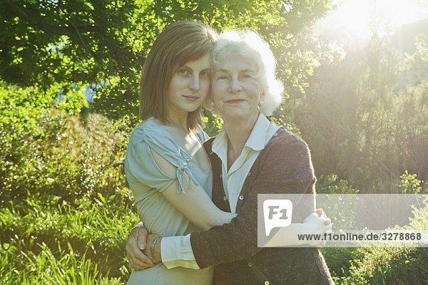 Großmutter und Enkelin umarmend Großmutter und Enkelin umarmend