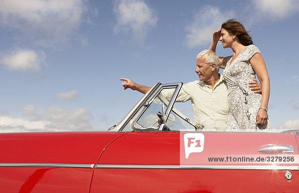 Seniorenpaar im Sportwagen  zeigend