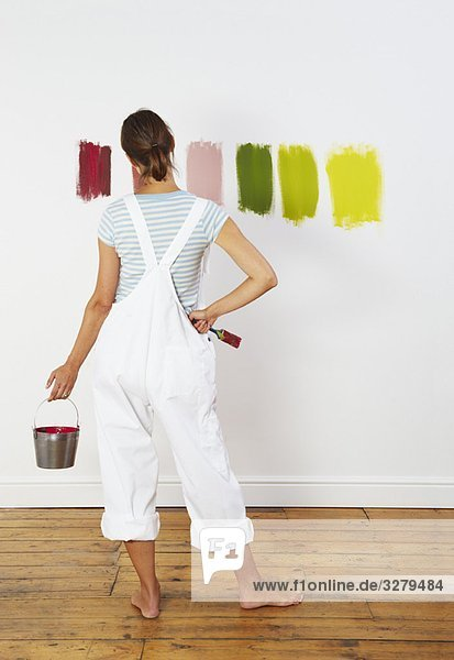 Frau betrachtet Farbmuster an der Wand
