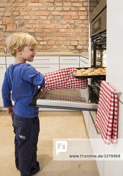 Junge nimmt gebackene Kekse aus dem Ofen