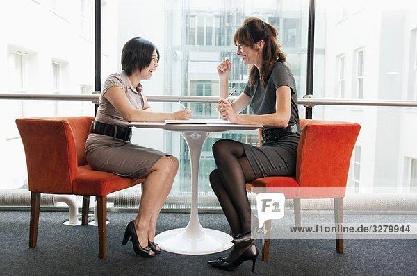 Weibliches Paar  das in einem Restaurant arbeitet.
