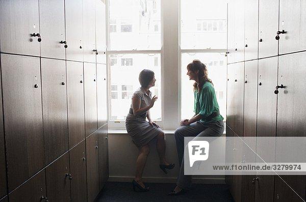 Zwei Geschäftsfrauen reden in einem Spind.