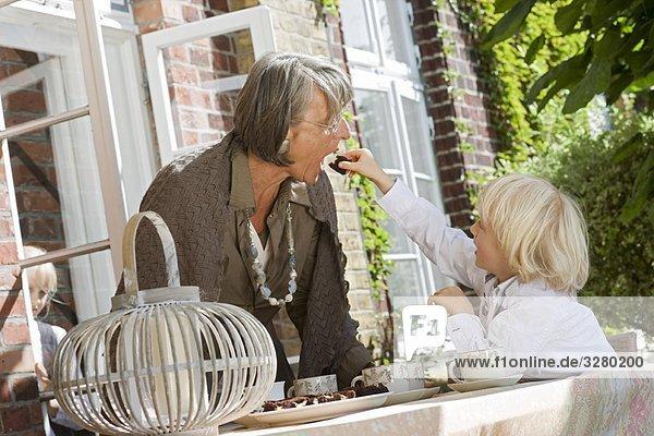 Enkel füttert Oma mit Kuchen Enkel füttert Oma mit Kuchen