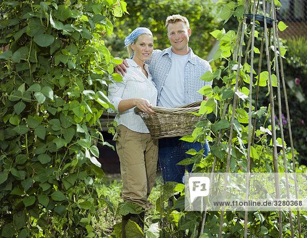 Junges Paar zwischen Bohnenpflanzen
