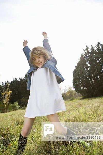 Mädchen in der Natur mit erhobenen Armen