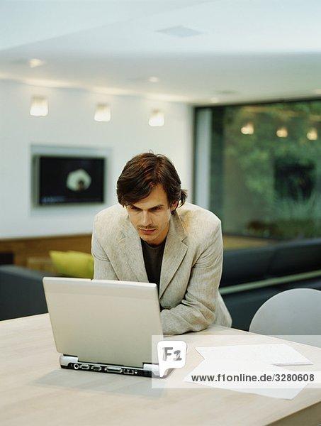 Ein junger  trendiger Mann arbeitet von zu Hause aus.