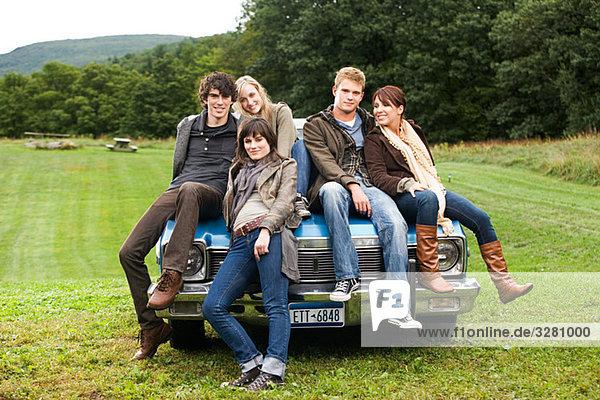 Friends sitting on a car