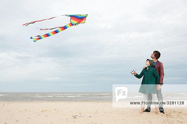 Junges Paar mit Drachen am Meer