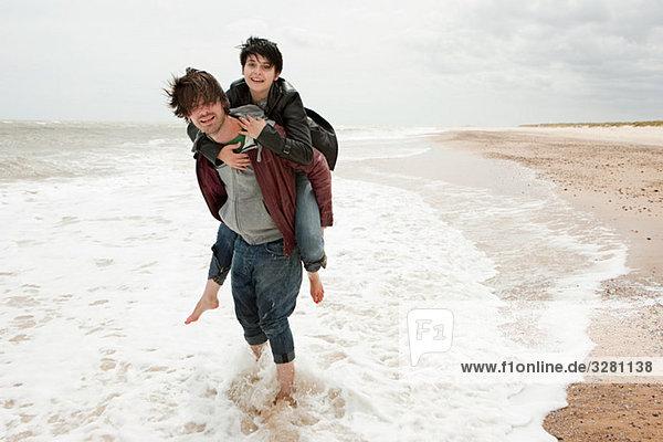 man giving girlfriend piggyback in the sea