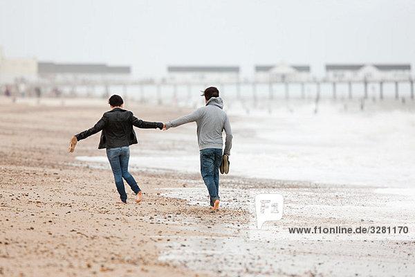Ein Paar läuft Hand in Hand am Meer.