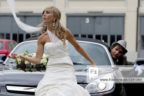 Braut vor einem Auto  Bräutigam im Hintergrund