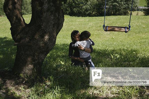 Eine Frau und ein Junge  die sich unter einem Baum umarmen.