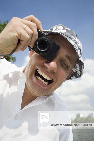 Ein ekstatischer Mann beim Fotografieren mit einer Digitalkamera