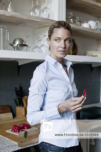 Ein Stehen in der Küche und das Halten eines Stückchens roter Pfeffer