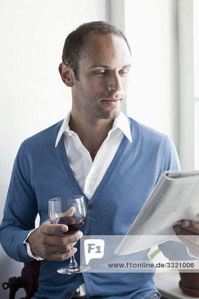 Ein Mann  der ein Glas Wein trinkt und eine Zeitschrift liest.