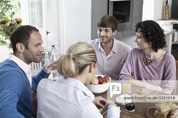 Eine Gruppe von Freunden  die zusammen am Esstisch sitzen.