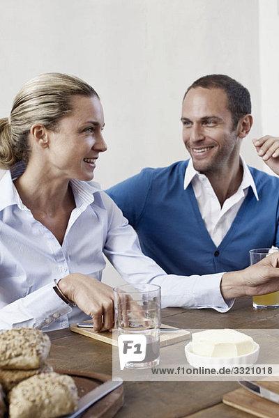 Ein Paar sitzt zusammen am Esstisch und lächelt.