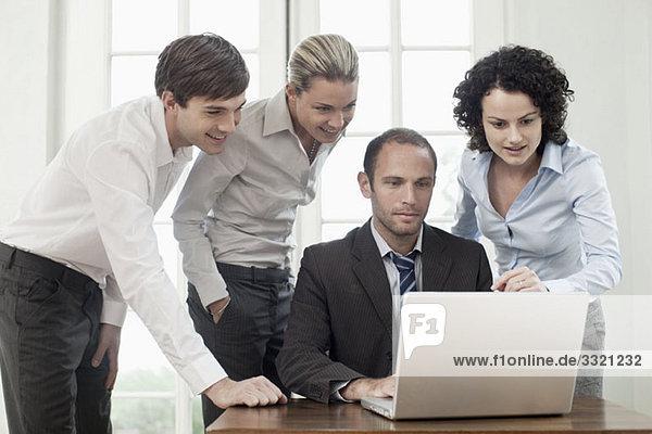 Geschäftskollegen um einen Laptop versammelt