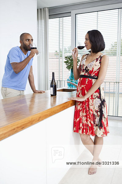A young couple drinking red wine