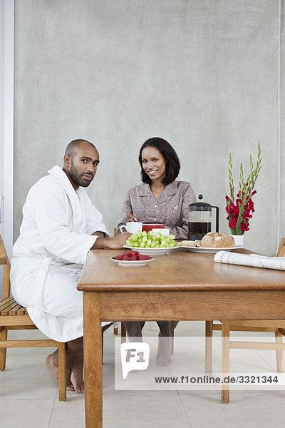 Ein junges Paar sitzt zum Frühstück an einem Tisch.
