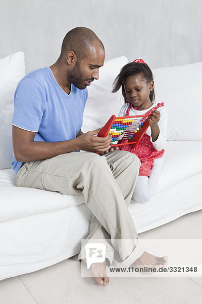 A father showing his young daughter how to use an abacus