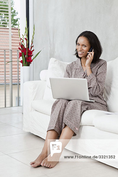 Eine Frau im Schlafanzug mit Laptop und Handy