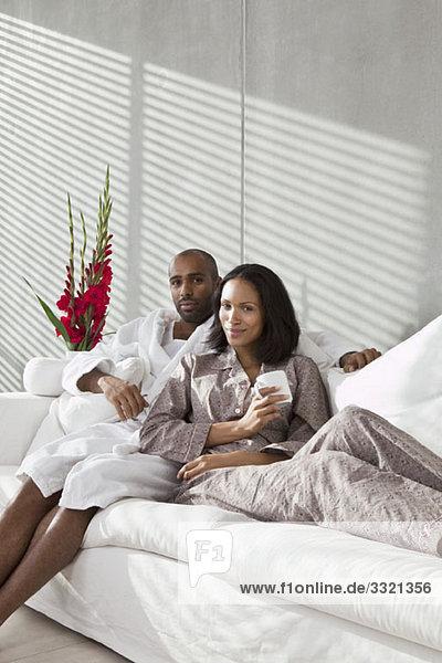 Portrait eines jungen Paares auf einem Sofa