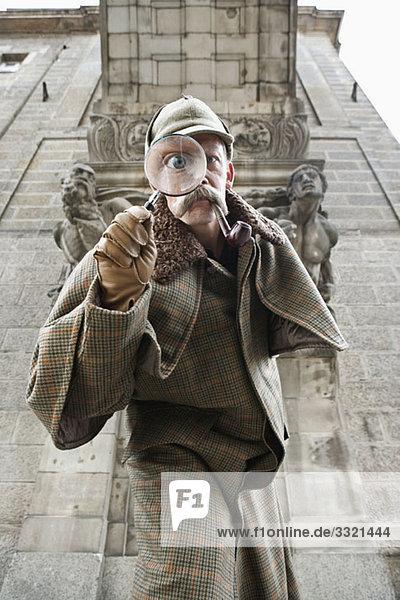 Ein Mann verkleidet als Sherlock Holmes mit einer Lupe  die sein Auge verzerrt.