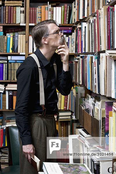 Ein Mann  der Bücher in einer Buchhandlung untersucht.