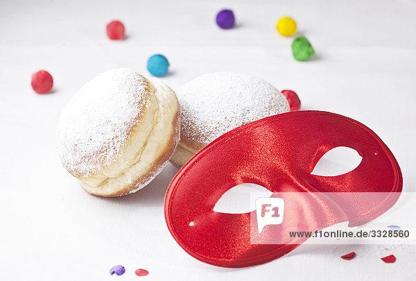 Rote Karnevalsmaske  Krapfen und Konfetti  Close-up