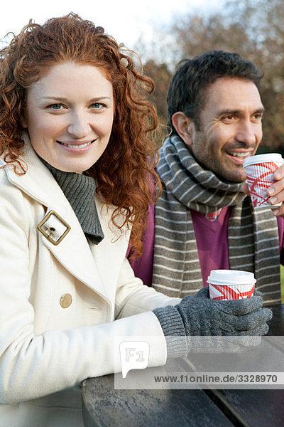 Ein glückliches Paar sitzt an einem Parktisch