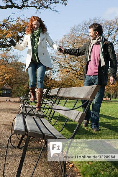 Eine Frau  die über eine Parkbank läuft.