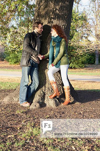 Ein Paar steht von Angesicht zu Angesicht neben einem Baum.