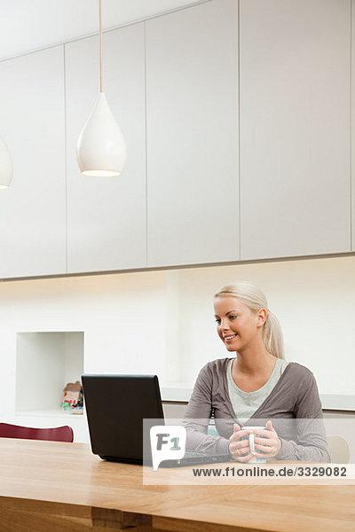 Junge Frau am Tisch sitzend mit Laptop