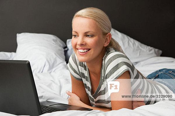 Junge Frau auf dem Bett liegend mit Laptop