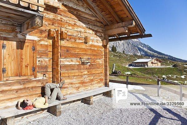 Frau rastet vor einer Almhütte  Mühlbach  Pongau  Salzburger Land  Österreich