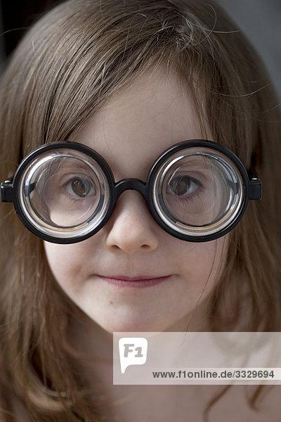 Kleines Mädchen mit dicken Brille auf spielen