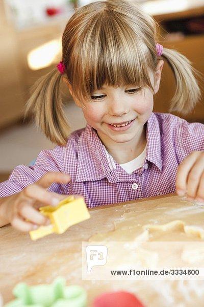 junges Mädchen schneidet Kekse