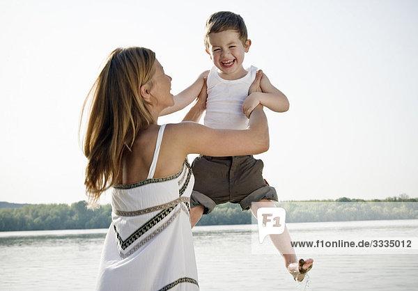 Mutter hebt Kind in die Luft