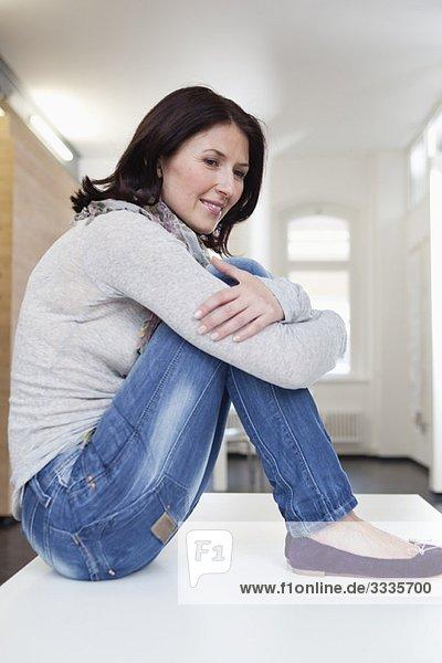 lächelnde Frau auf dem Tisch sitzend