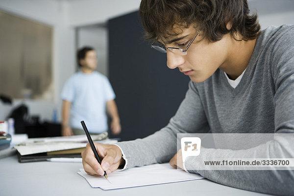 Studentisches Schreiben am Schreibtisch im Klassenzimmer